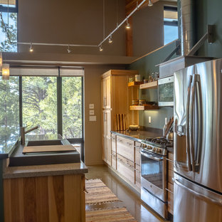 This is an example of a mid-sized modern kitchen in Phoenix with flat-panel cabinets, recycled glass benchtops, stainless steel appliances, concrete floors, with island and multi-coloured floor.