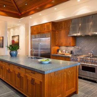 Idéer för tropiska kök, med en undermonterad diskho, skåp i shakerstil, skåp i mellenmörkt trä, grått stänkskydd, stänkskydd i sten, rostfria vitvaror och en köksö