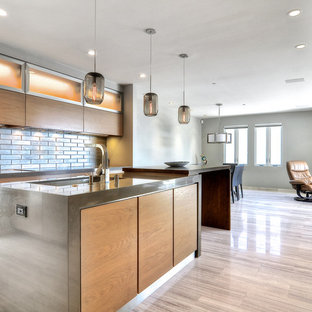 Photo of a large modern l-shaped open plan kitchen in San Francisco with an undermount sink, flat-panel cabinets, light wood cabinets, zinc benchtops, metallic splashback, metal splashback, stainless steel appliances, ceramic floors, with island and beige floor.