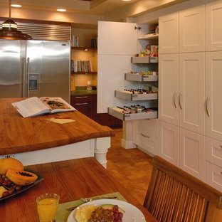 Inspiration for a tropical eat-in kitchen in Hawaii with stainless steel appliances, wood benchtops, shaker cabinets, white cabinets and cork floors.
