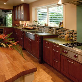 Tropical eat-in kitchen in Hawaii with a farmhouse sink, wood benchtops, glass tile splashback, stainless steel appliances, shaker cabinets, medium wood cabinets, multi-coloured splashback, cork floors and green benchtop.