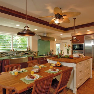 Tropical eat-in kitchen in Hawaii with stainless steel appliances, wood benchtops, a farmhouse sink, glass tile splashback and green benchtop.