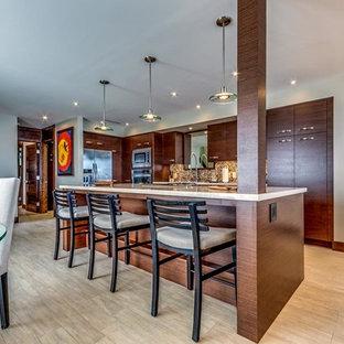 Cette photo montre une cuisine américaine bord de mer en L de taille moyenne avec un placard à porte plane, des portes de placard en bois sombre, une crédence marron, un électroménager en acier inoxydable et un îlot central.