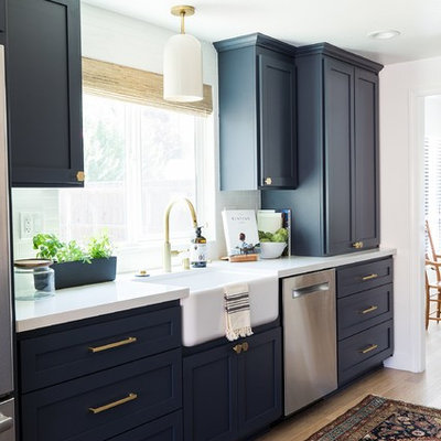 Kitchen - country medium tone wood floor and beige floor kitchen idea in Sacramento with a farmhouse sink, shaker cabinets, black cabinets, white backsplash, brick backsplash, stainless steel appliances, no island and white countertops