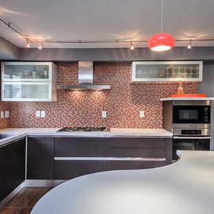 На фото: угловые кухни среднего размера в современном стиле с обеденным столом, монолитной раковиной, плоскими фасадами, черными фасадами, столешницей из кварцевого агломерата, оранжевым фартуком, фартуком из плитки мозаики, техникой из нержавеющей стали и островом
