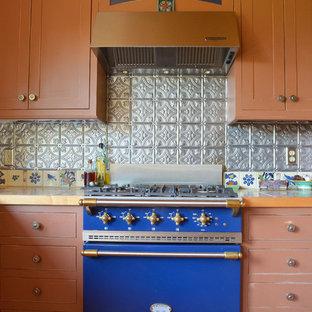 Exemple d'une cuisine montagne avec une crédence en dalle métallique, un électroménager de couleur, un plan de travail en carrelage, une crédence métallisée et un placard à porte shaker.