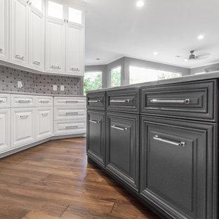 Große Klassische Küche in U-Form mit Vorratsschrank, Landhausspüle, profilierten Schrankfronten, grauen Schränken, Quarzit-Arbeitsplatte, Küchenrückwand in Grau, Kalk-Rückwand, Küchengeräten aus Edelstahl, dunklem Holzboden, Halbinsel, braunem Boden und grauer Arbeitsplatte in Houston