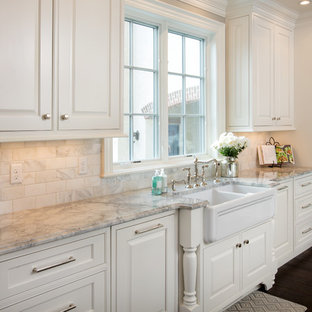 Example of a large classic galley medium tone wood floor enclosed kitchen design in Columbus with a farmhouse sink, recessed-panel cabinets, white cabinets, granite countertops, multicolored backsplash, white appliances, an island and subway tile backsplash