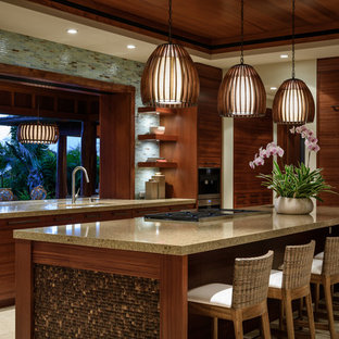 This is an example of a large tropical u-shaped open plan kitchen in Hawaii with an undermount sink, flat-panel cabinets, medium wood cabinets, quartz benchtops, blue splashback, glass tile splashback, panelled appliances, limestone floors and with island.