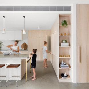 メルボルンの大きいコンテンポラリースタイルのおしゃれなコの字型キッチン (アンダーカウンターシンク、淡色木目調キャビネット、コンクリートカウンター、白いキッチンパネル、レンガのキッチンパネル、シルバーの調理設備の、コンクリートの床、アイランドなし) の写真