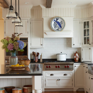 Traditional eat-in kitchen appliance - Eat-in kitchen - traditional u-shaped eat-in kitchen idea in Boston with stainless steel appliances, granite countertops, a farmhouse sink, recessed-panel cabinets, white cabinets, white backsplash and subway tile backsplash