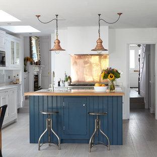 Bild på ett industriellt kök och matrum, med en undermonterad diskho, skåp i shakerstil, vita skåp, stänkskydd med metallisk yta, stänkskydd i metallkakel, rostfria vitvaror och en köksö