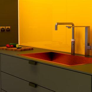 Einzeilige Moderne Wohnküche mit Unterbauwaschbecken, flächenbündigen Schrankfronten, grünen Schränken, Mineralwerkstoff-Arbeitsplatte, Küchenrückwand in Gelb, Rückwand aus Glasfliesen, schwarzen Elektrogeräten, braunem Holzboden, Kücheninsel und grüner Arbeitsplatte in Dublin