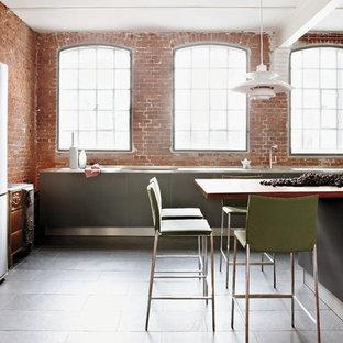 ハンブルクの中サイズのインダストリアルスタイルのおしゃれなキッチン (フラットパネル扉のキャビネット、グレーのキャビネット、ステンレスカウンター、レンガのキッチンパネル、シルバーの調理設備、スレートの床、黒い床) の写真