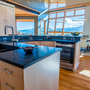 Photo of a mid-sized modern u-shaped eat-in kitchen in Denver with flat-panel cabinets, light wood cabinets, limestone benchtops, blue splashback, glass tile splashback, stainless steel appliances, light hardwood floors, with island and brown floor.