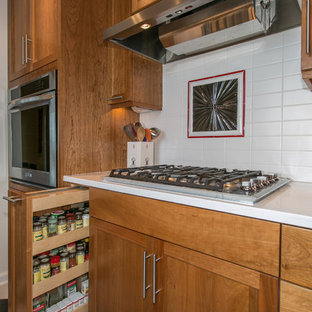 Photo of a mid-sized country galley eat-in kitchen in Portland with an undermount sink, shaker cabinets, medium wood cabinets, quartz benchtops, white splashback, ceramic splashback, stainless steel appliances, porcelain floors and no island.
