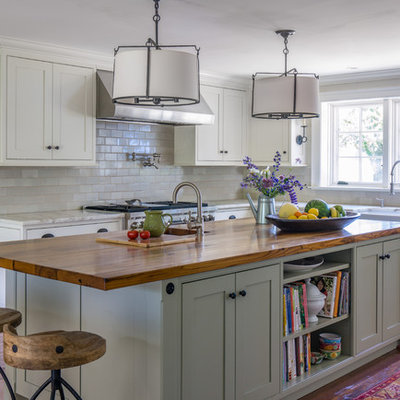 Eat-in kitchen - large farmhouse l-shaped medium tone wood floor eat-in kitchen idea in Boston with a farmhouse sink, recessed-panel cabinets, white cabinets, wood countertops, white backsplash, ceramic backsplash, stainless steel appliances and an island