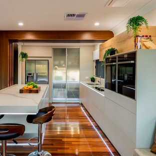 Design ideas for a large contemporary l-shaped eat-in kitchen in Brisbane with flat-panel cabinets, beige cabinets, quartz benchtops, black appliances, medium hardwood floors, with island, brown floor and white benchtop.