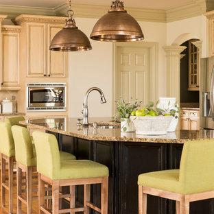 Idee per una grande cucina chic con ante beige, top in granito, isola, lavello sottopiano, ante con riquadro incassato, elettrodomestici in acciaio inossidabile e pavimento in legno massello medio