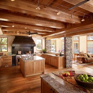 トロントのサンタフェスタイルのおしゃれなキッチン (落し込みパネル扉のキャビネット、淡色木目調キャビネット、御影石カウンター、シルバーの調理設備の、無垢フローリング) の写真