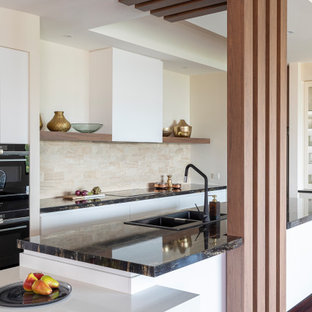 Inspiration for a large contemporary galley open plan kitchen in Brisbane with a drop-in sink, flat-panel cabinets, white cabinets, granite benchtops, beige splashback, stone tile splashback, black appliances, medium hardwood floors, brown floor, black benchtop and a peninsula.