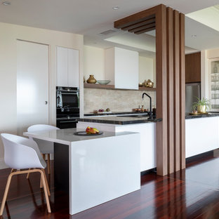 This is an example of a contemporary l-shaped kitchen in Brisbane with flat-panel cabinets, white cabinets, beige splashback, black appliances, dark hardwood floors, with island, brown floor and black benchtop.