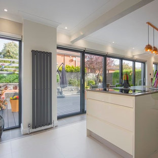 Mid-sized contemporary single-wall open plan kitchen in Other with louvered cabinets, white cabinets, slate floors, with island and grey floor.