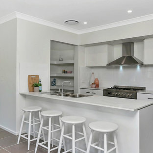 Design ideas for a mid-sized contemporary kitchen in Central Coast with a drop-in sink, flat-panel cabinets, white cabinets, white splashback, stainless steel appliances, a peninsula, grey floor and white benchtop.