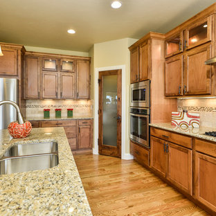 Traditional kitchen designs - Elegant kitchen photo in Denver with recessed-panel cabinets and medium tone wood cabinets
