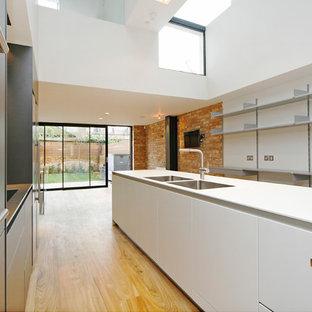 ロンドンの広いコンテンポラリースタイルのおしゃれなキッチン (ドロップインシンク、フラットパネル扉のキャビネット、白いキャビネット、人工大理石カウンター、白いキッチンパネル、ガラス板のキッチンパネル、パネルと同色の調理設備、淡色無垢フローリング、黄色い床、白いキッチンカウンター) の写真