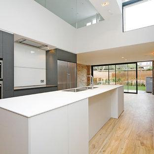 ロンドンの大きいコンテンポラリースタイルのおしゃれなキッチン (ドロップインシンク、フラットパネル扉のキャビネット、白いキャビネット、人工大理石カウンター、白いキッチンパネル、ガラス板のキッチンパネル、パネルと同色の調理設備、淡色無垢フローリング、黄色い床、白いキッチンカウンター) の写真