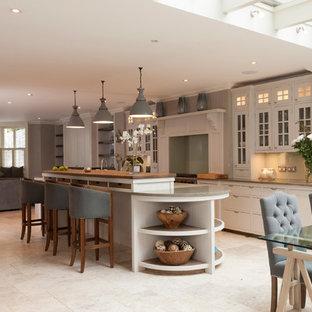 Klassisk inredning av ett stort kök, med en rustik diskho, grå skåp, granitbänkskiva, grönt stänkskydd, glaspanel som stänkskydd, rostfria vitvaror, skåp i shakerstil, klinkergolv i porslin och en köksö