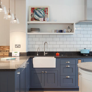 Photo of a medium sized contemporary kitchen/diner in London with a belfast sink, beaded cabinets, blue cabinets, granite worktops, white splashback, metro tiled splashback and an island.