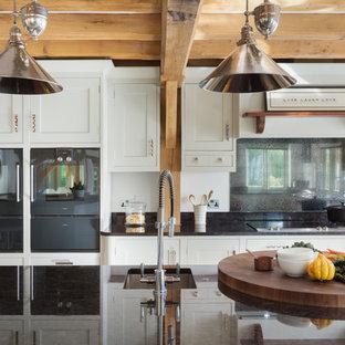 Ispirazione per una cucina parallela country con ante in stile shaker, top in granito, paraspruzzi a effetto metallico, isola, lavello sottopiano, ante bianche e elettrodomestici neri