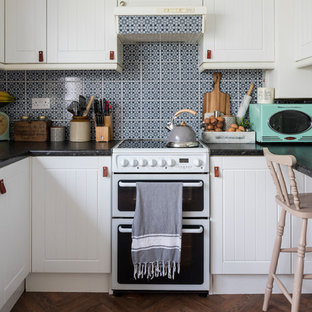 This is an example of a small vintage u-shaped kitchen/diner in London with beaded cabinets, white cabinets, multi-coloured splashback, a breakfast bar and brown floors.