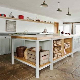 Lantlig inredning av ett kök, med öppna hyllor och en köksö