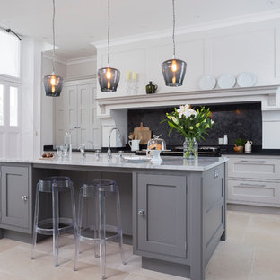 Large transitional open plan kitchen in Hampshire with grey cabinets, black splashback, with island, a double-bowl sink, beaded inset cabinets, granite benchtops and limestone floors.