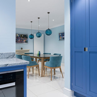 Design ideas for a mid-sized contemporary l-shaped open plan kitchen in Hampshire with a drop-in sink, shaker cabinets, blue cabinets, granite benchtops, grey splashback, marble splashback, white appliances, ceramic floors, with island, white floor and grey benchtop.