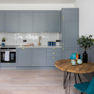 Inspiration for a small contemporary single-wall kitchen/diner in Hertfordshire with a submerged sink, shaker cabinets, grey cabinets, quartz worktops, white splashback, black appliances, no island, white worktops, medium hardwood flooring and beige floors.