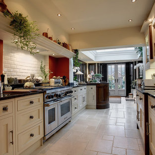 Photo of a medium sized galley kitchen/diner in Gloucestershire with a submerged sink, recessed-panel cabinets, yellow cabinets, granite worktops, white splashback, metro tiled splashback, stainless steel appliances, limestone flooring and no island.