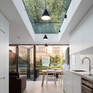 This is an example of a contemporary galley kitchen in London with a submerged sink, flat-panel cabinets, white cabinets, stainless steel appliances, no island, marble worktops, white splashback and ceramic flooring.
