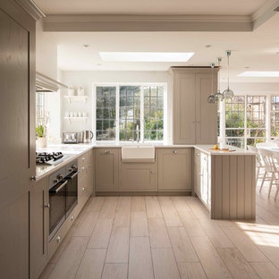 Design ideas for a medium sized farmhouse u-shaped kitchen in London with a belfast sink, recessed-panel cabinets, beige cabinets, stainless steel appliances and beige floors.