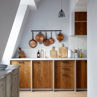 Inspiration for a large scandinavian galley open plan kitchen in London with a drop-in sink, recessed-panel cabinets, medium wood cabinets, terrazzo benchtops, black appliances and no island.