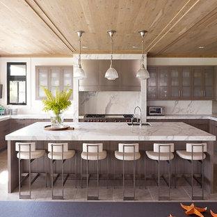 Foto på ett funkis u-kök, med luckor med glaspanel, en enkel diskho, bruna skåp, vitt stänkskydd, stänkskydd i sten och integrerade vitvaror