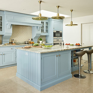 Large traditional single-wall open plan kitchen in Oxfordshire with a single-bowl sink, shaker cabinets, blue cabinets, granite worktops, stainless steel appliances, an island, white splashback, metro tiled splashback, grey floors and grey worktops.