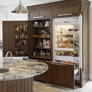 Diseño de cocina clásica renovada con encimera de granito, despensa, fregadero bajoencimera, armarios estilo shaker, puertas de armario de madera en tonos medios, electrodomésticos con paneles, una isla, suelo beige y suelo de piedra caliza