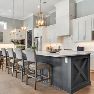 Example of a coastal light wood floor and beige floor kitchen design in Atlanta with shaker cabinets, white cabinets, white backsplash, subway tile backsplash, stainless steel appliances and an island