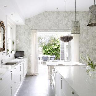 Стильный дизайн: кухня в современном стиле с обеденным столом, врезной раковиной, стеклянными фасадами, белыми фасадами и островом - последний тренд