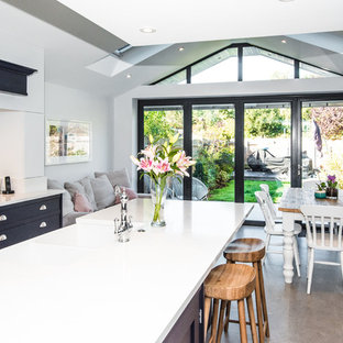 Photo of a medium sized contemporary u-shaped open plan kitchen in London with a submerged sink, blue cabinets, granite worktops, white splashback, ceramic flooring, an island, grey floors and white worktops.