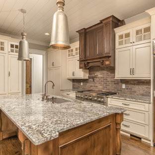 Large craftsman eat-in kitchen pictures - Eat-in kitchen - large craftsman single-wall dark wood floor eat-in kitchen idea in Other with an undermount sink, recessed-panel cabinets, beige cabinets, granite countertops, red backsplash, brick backsplash, stainless steel appliances and an island